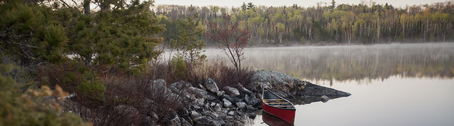 Red Canoe on misty northern lake.png