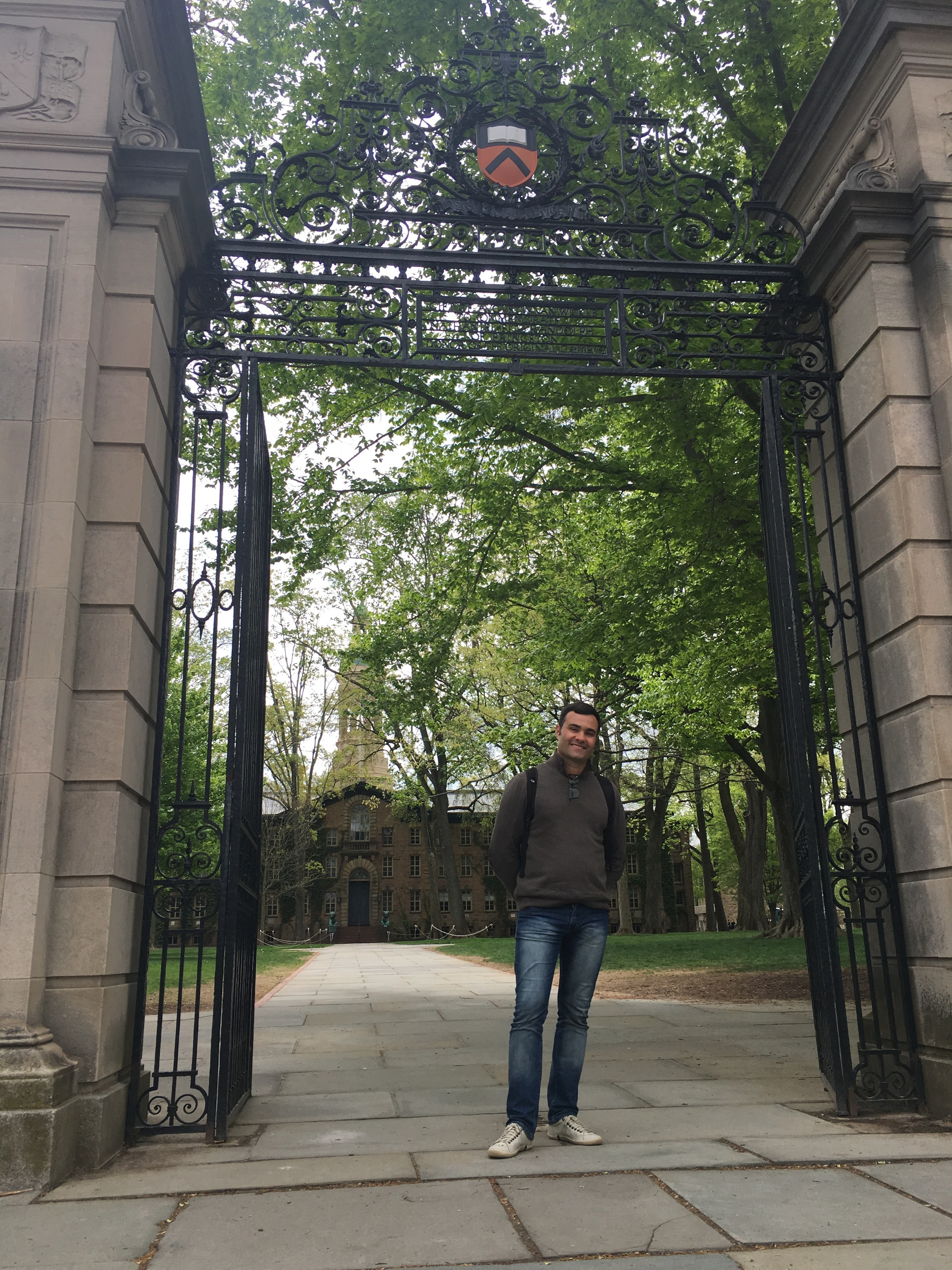 Murilo standing at the Fitz-Randolph Gates in front of Nassau Hall, the oldest building on campus.