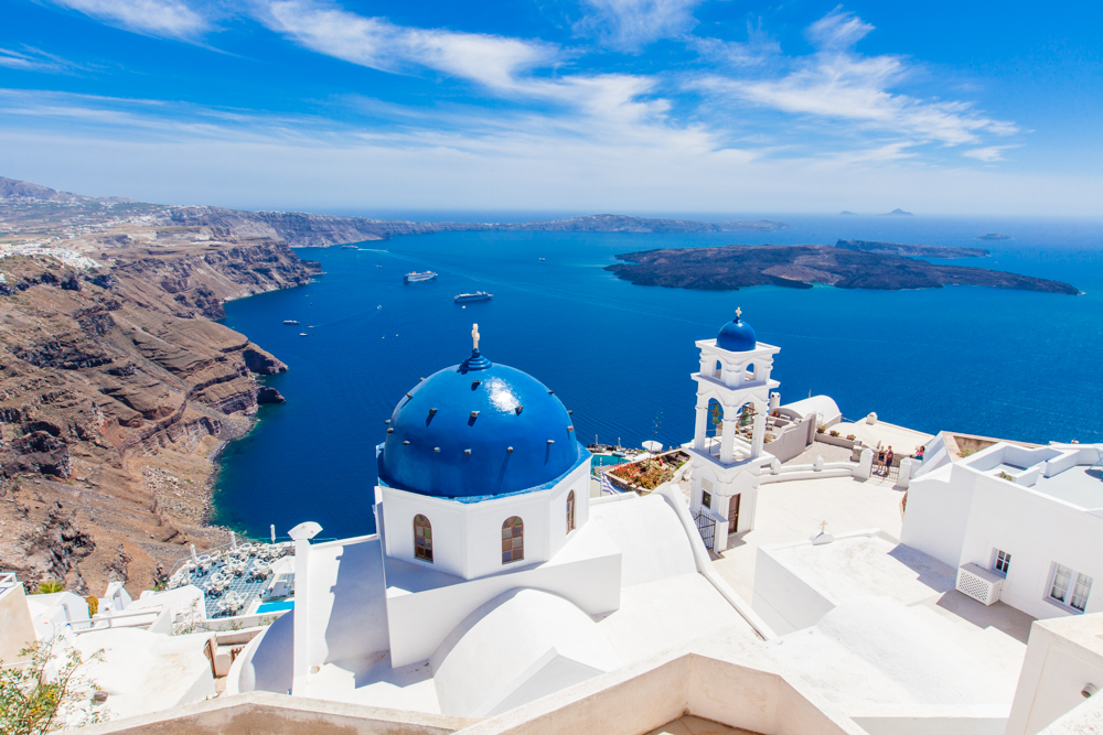 The blue domes of the church match the deep blue sky and sea below.