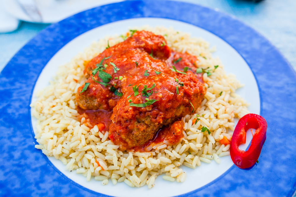 Soutzoukakia with rice - cumin flavored baked meatballs with tomato sauce