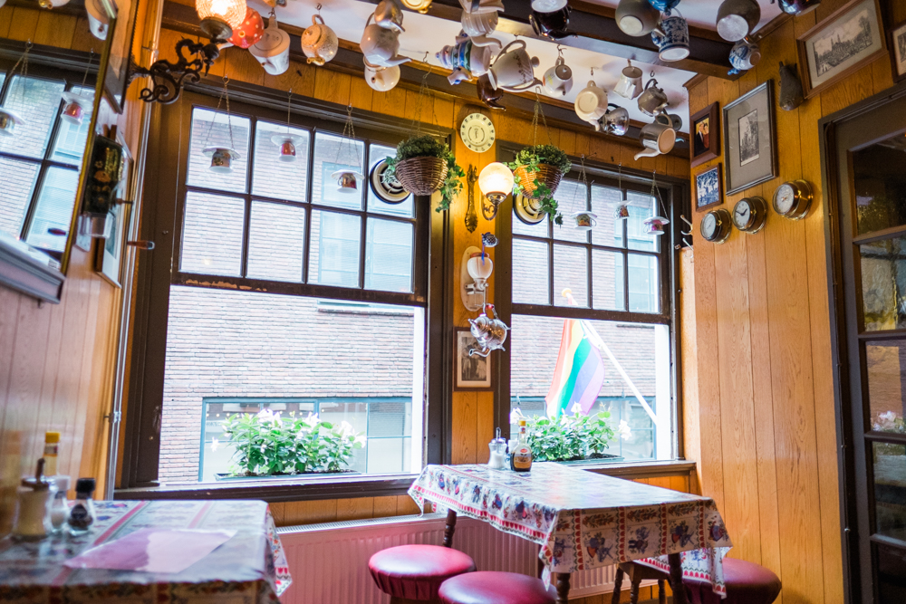 Two out of the four tables in the entire restaurant; upside down teapots hang from the ceiling of The Upstairs Pancake House.