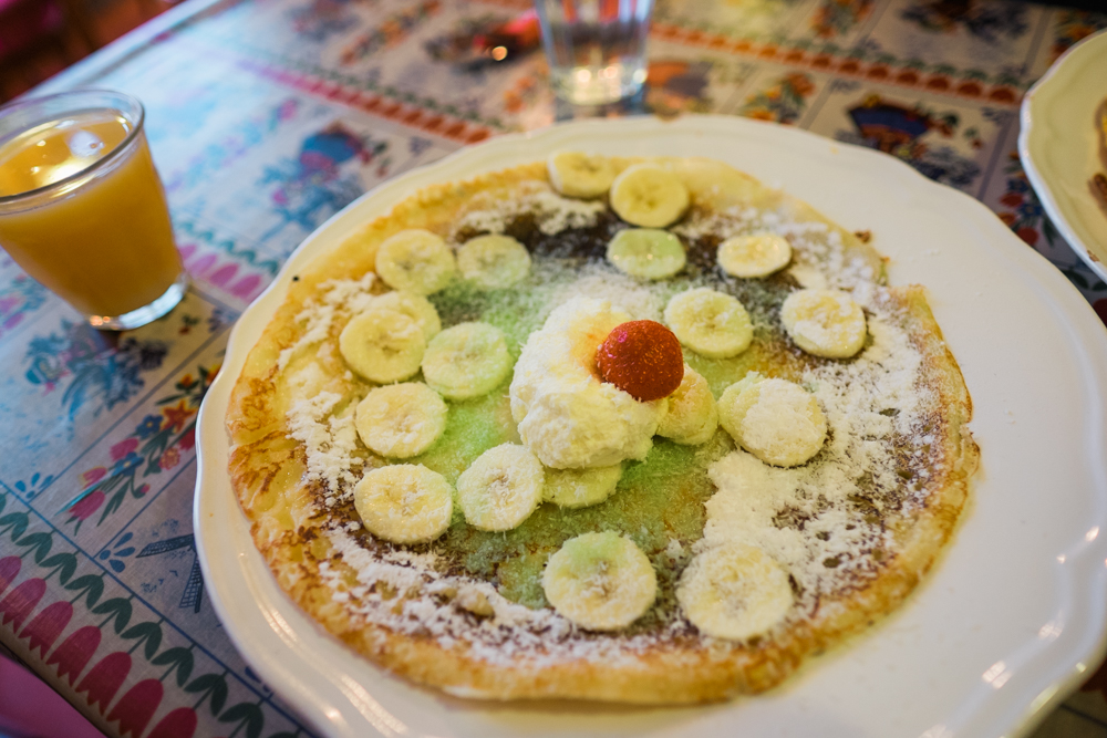 A sweet pancake with bananas, coconut, and cream