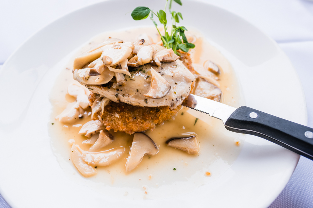 Chicken and mushrooms: sautéed boneless chicken breast served on a pesto potato cake with a local mushroom lemon sauce