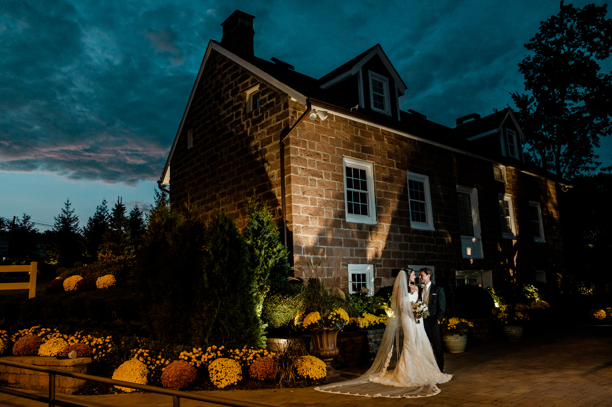 Photograph of Bride and Groom embracing under a blue dark sky at the historic cottage at The Gove with warm orange ambient light and fall decorations