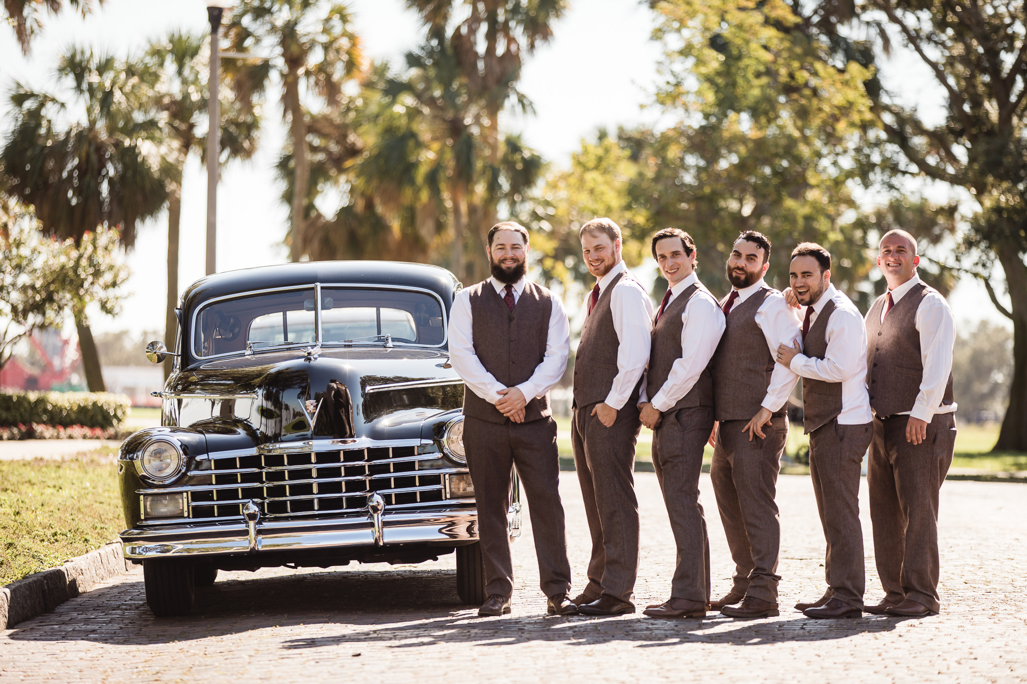 Grooms standing with groomsmen and a classic car before a wedding at Vinoy Park in St. Petersburg, Florida
