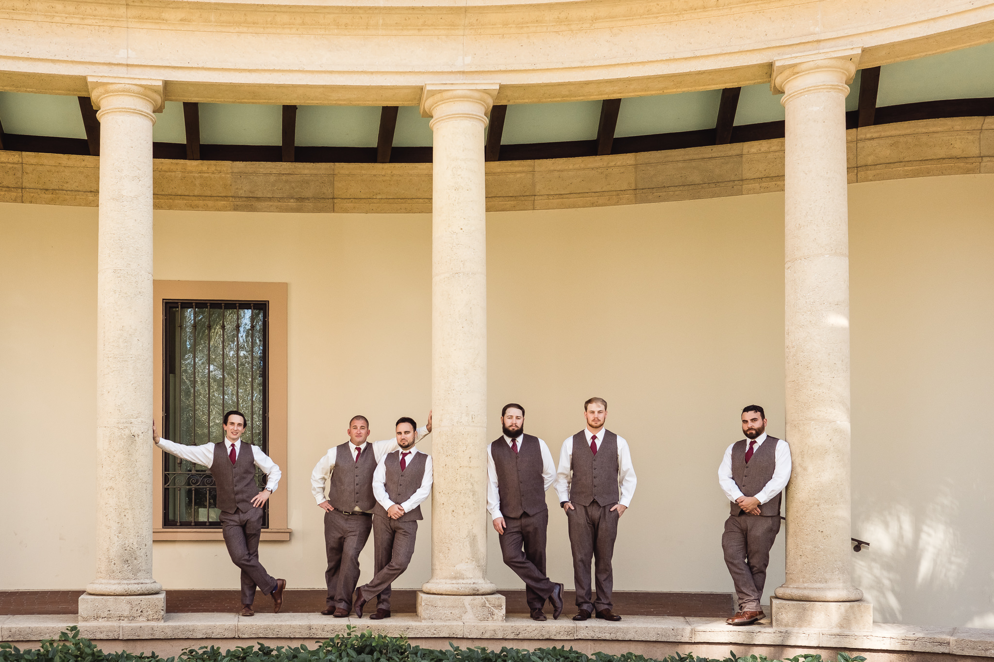 Groom and groomsmen pose by columns outside the Museum of Fine Arts in downtown St. Petersburg, Florida