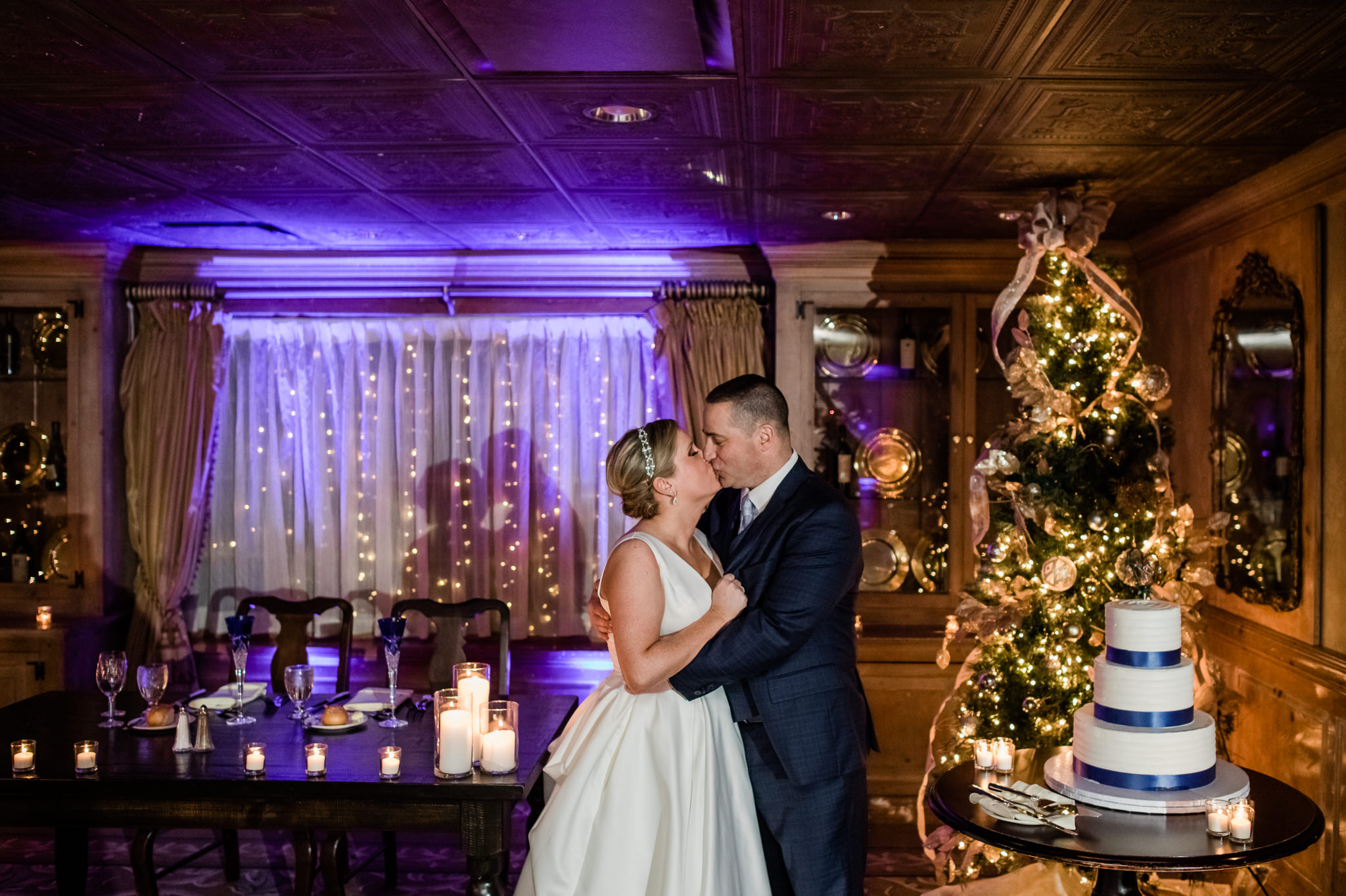 Bride and groom inside during their winter wedding at the grain house in basking ridge new jersey with blue and orange Christmas themed lights