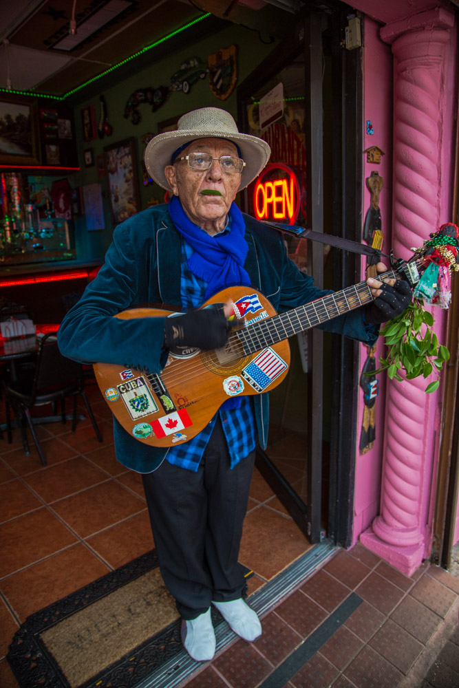 """Angel, Cuba American; likes to play the guitar around Calle 8 restaurants. He is also known as """"El Mago de la Hoja"""" (The Leaf Magician), because his leaf whistling skill accompanies his guitar tunes."""