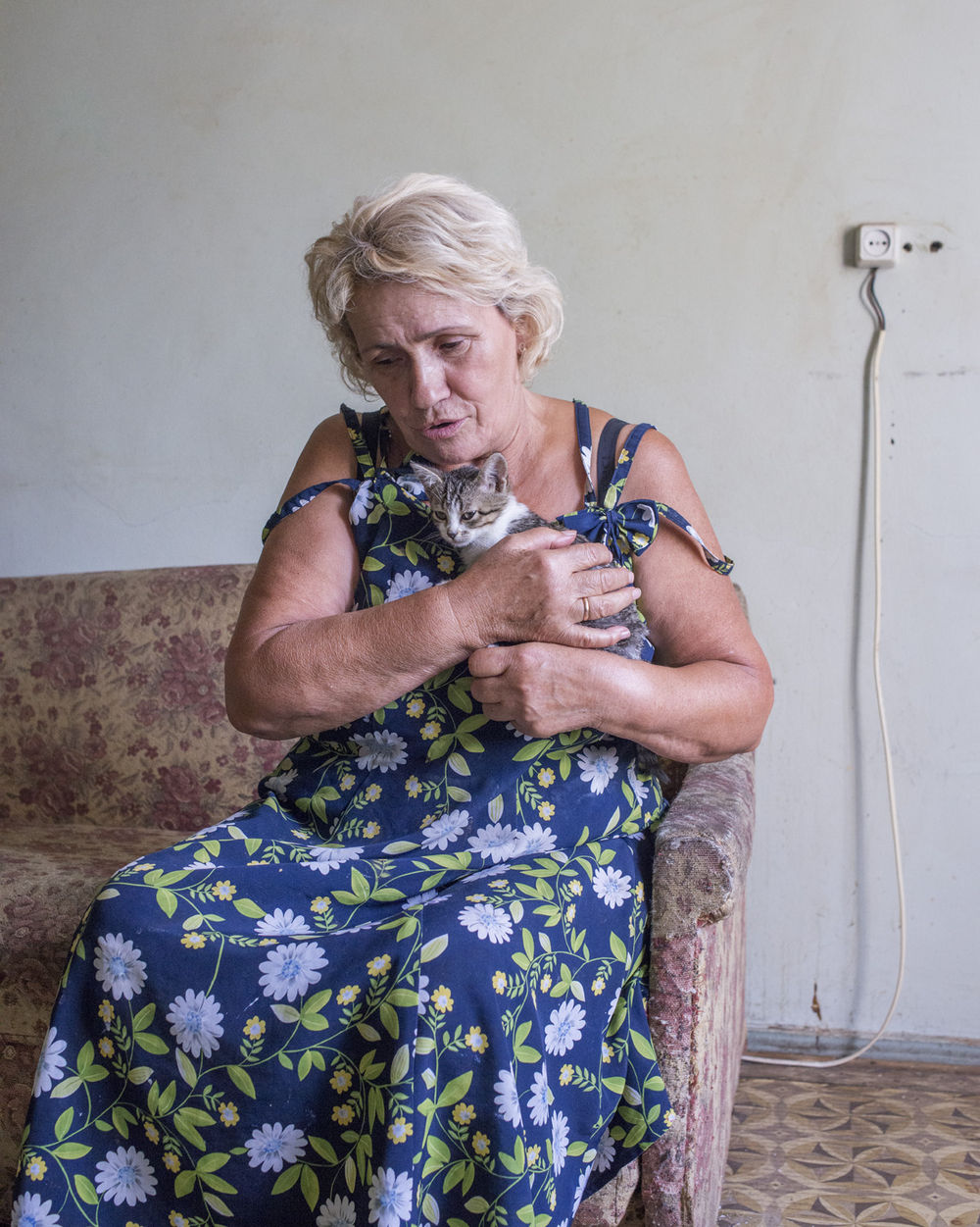 """Marie, 70, lives in the government-assisted shelter Collective Center after fleeing shelling in the east. """"This kitten is named Mariska. She heals me by taking away bad energy."""""""