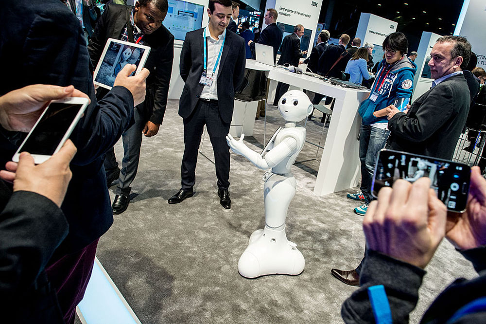 Visitors attend a demonstration of a robot named 'Pepper' at the IBM stand on day 3 of the Mobile World Congress 2016 on February 24, 2016 in Barcelona, Spain. The annual Mobile World Congress hosts some of the world's largest communications companies, with many unveiling their latest phones and wearables gadgets.  Photo:  David Ramos/Getty Images.
