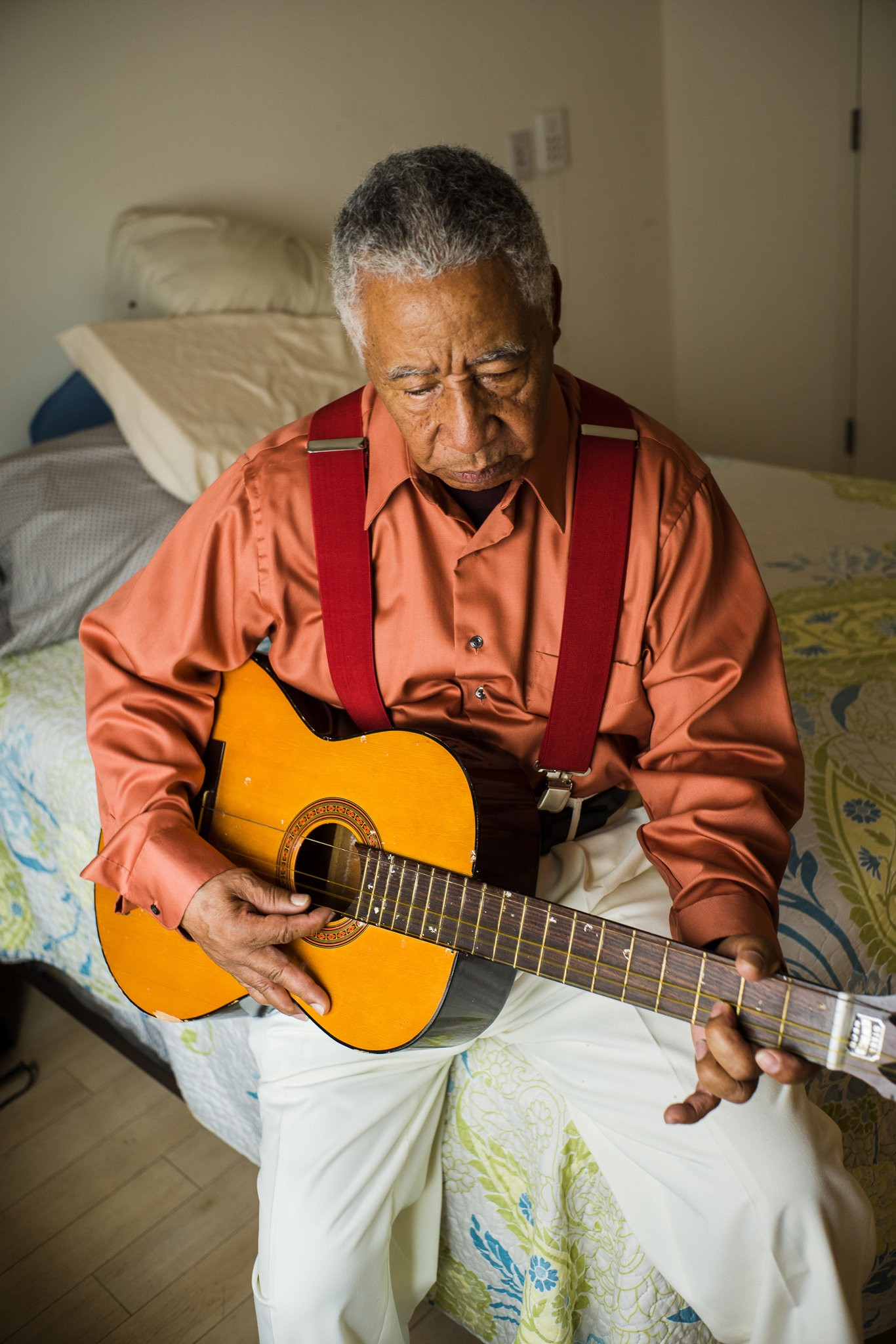 Olmedini strumming a guitar in his apartment in a housing complex for the disabled in East Harlem. credit: Jaime Permuth