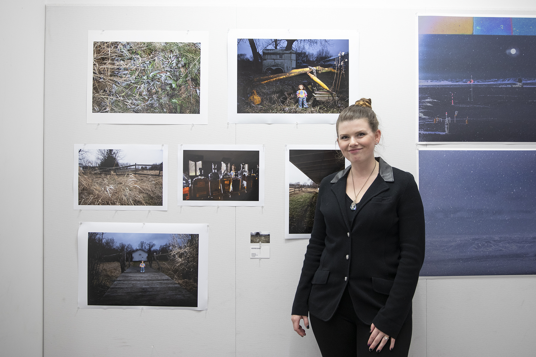 Heather Olker proudly stands with her prints at Salon