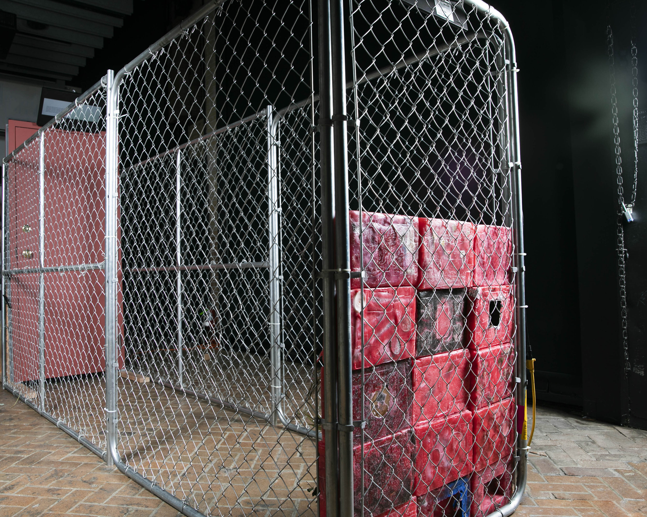 Traumatic Iterations , 2019, installation view, sculpture, 3 feet x  10 feet x 6 feet, votive wall, steel door, cage