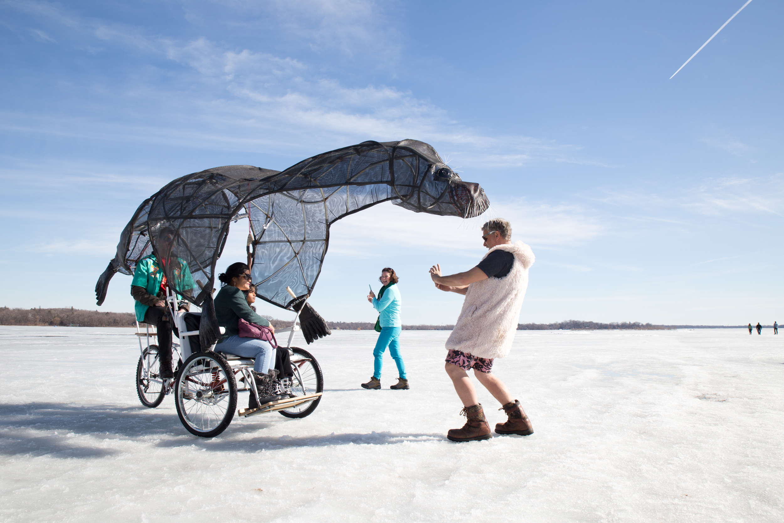 Artist Peter Shulze (in shorts!) takes a shot of his Seal Bike for some happy passengers