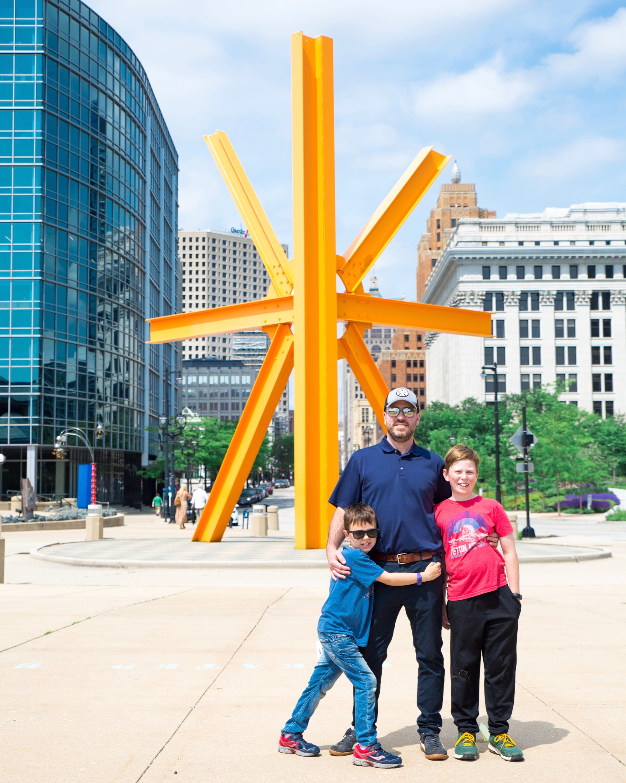 """My boys! They're standing in front of the Milwaukee-famous big orange sculpture """"The Calling."""" It was created by Mark di Suvero and installed in the 1980's."""