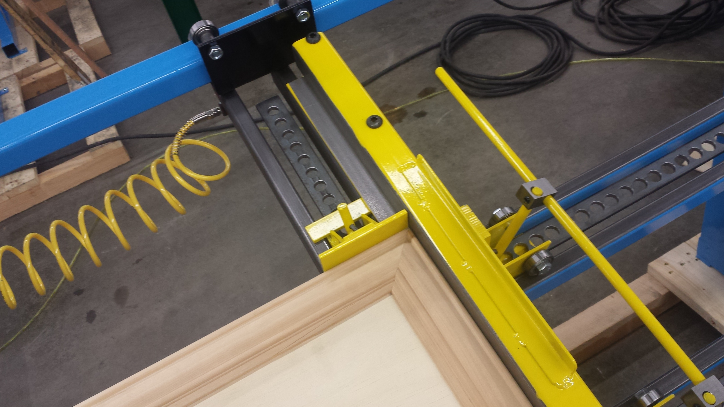 Miter door clamp controlspressure on both sides with pneumatic dialsallowing for fine adjustment.