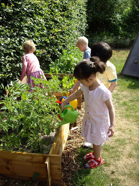 The children love to water their vegetables