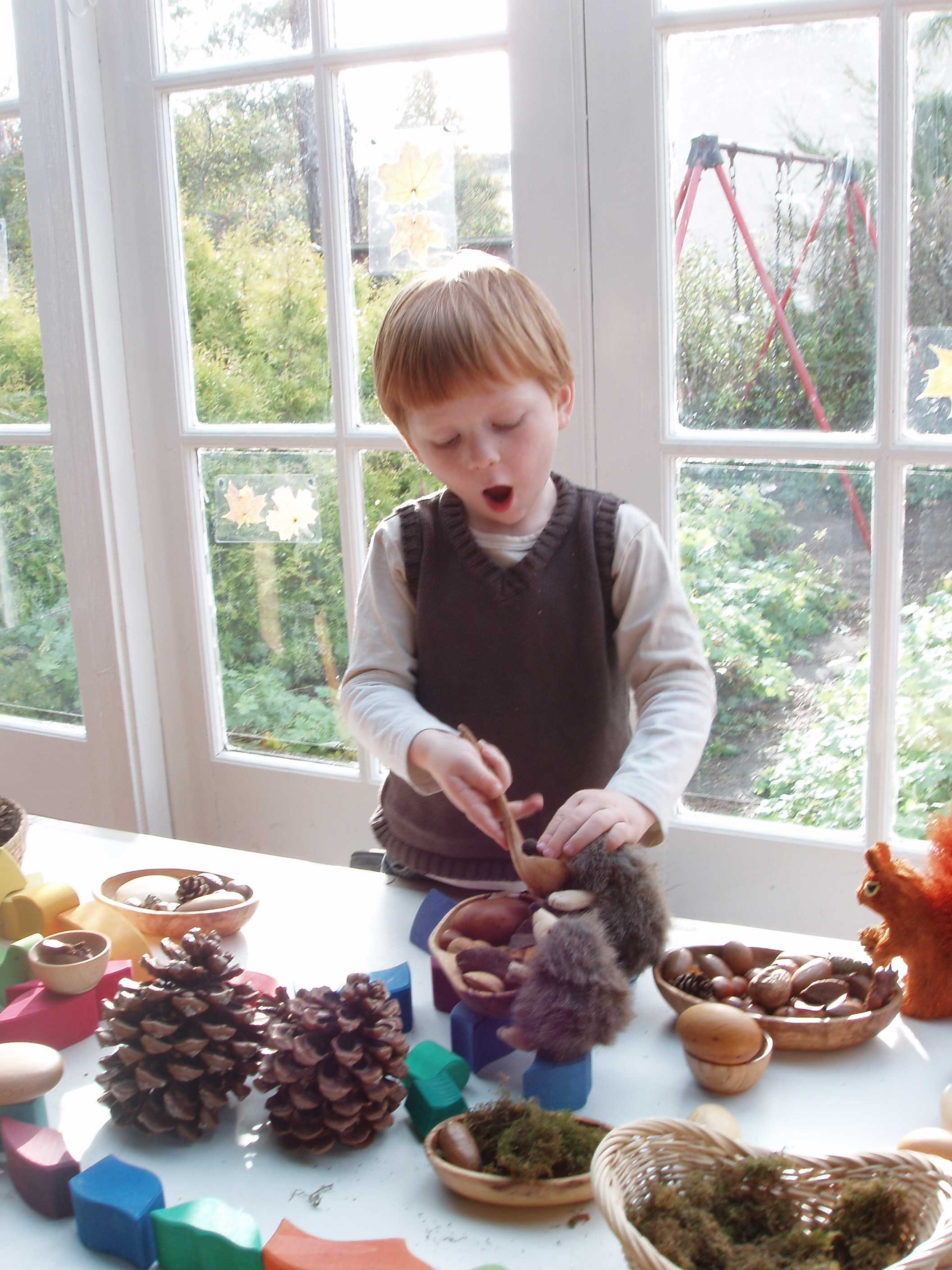 Using open ended natural 'loose parts' this boy is creating a cosy home and a meal for woodland animals.