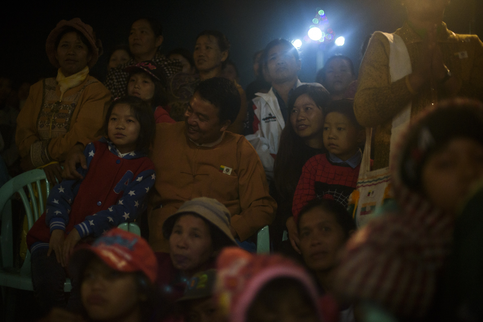 One Leng watches the concert with his wife, daughter and son amid a crowd of supporters.