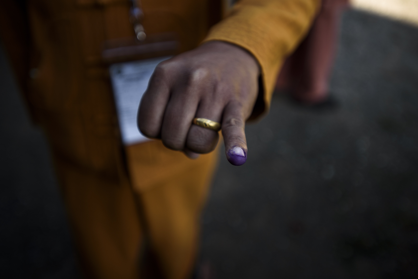 One Leng displays his finger stained with silver nitrate ink showing he has already voted.