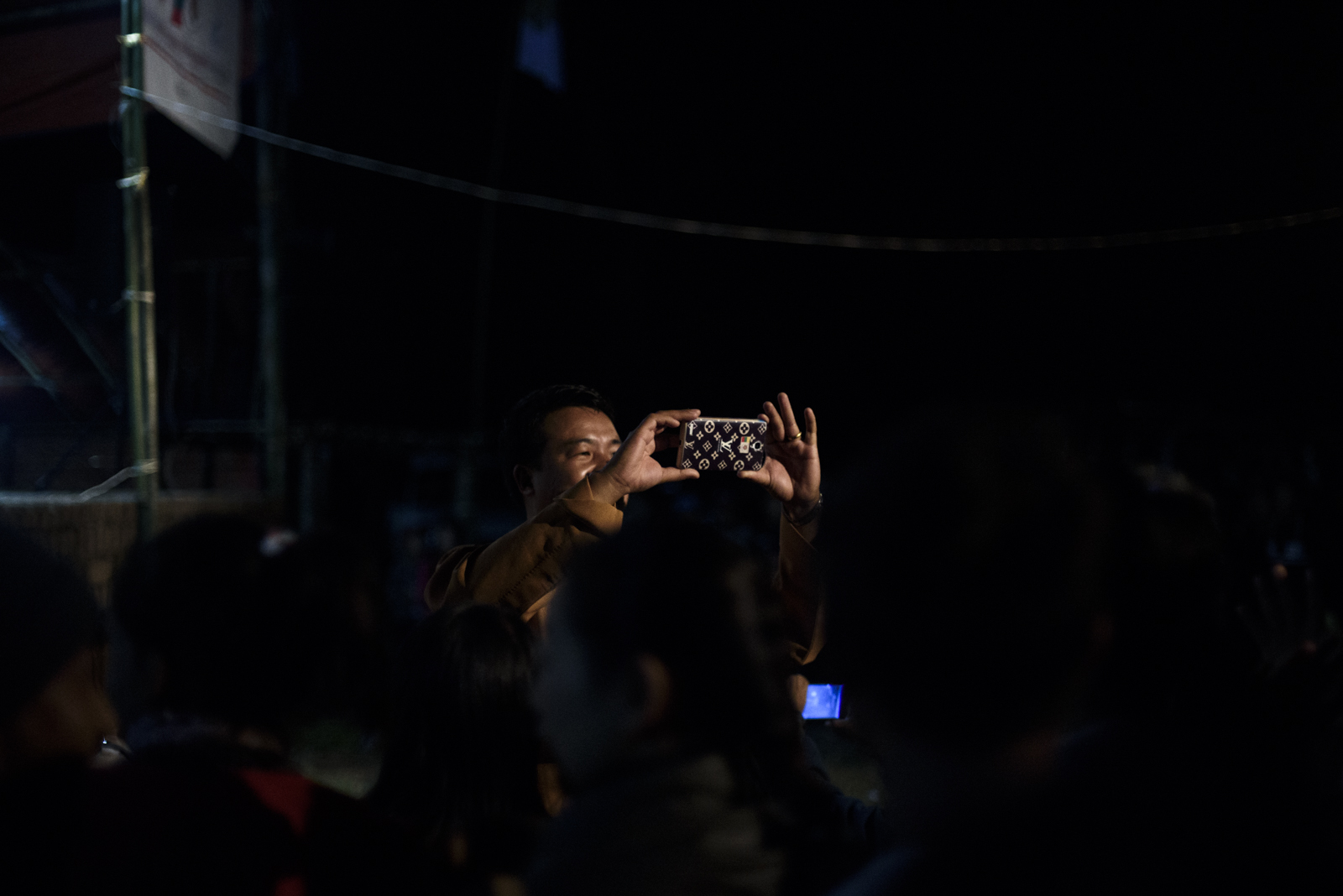 One Leng takes a photo of the crowd. He is constantly on Facebook posting campaign updates.