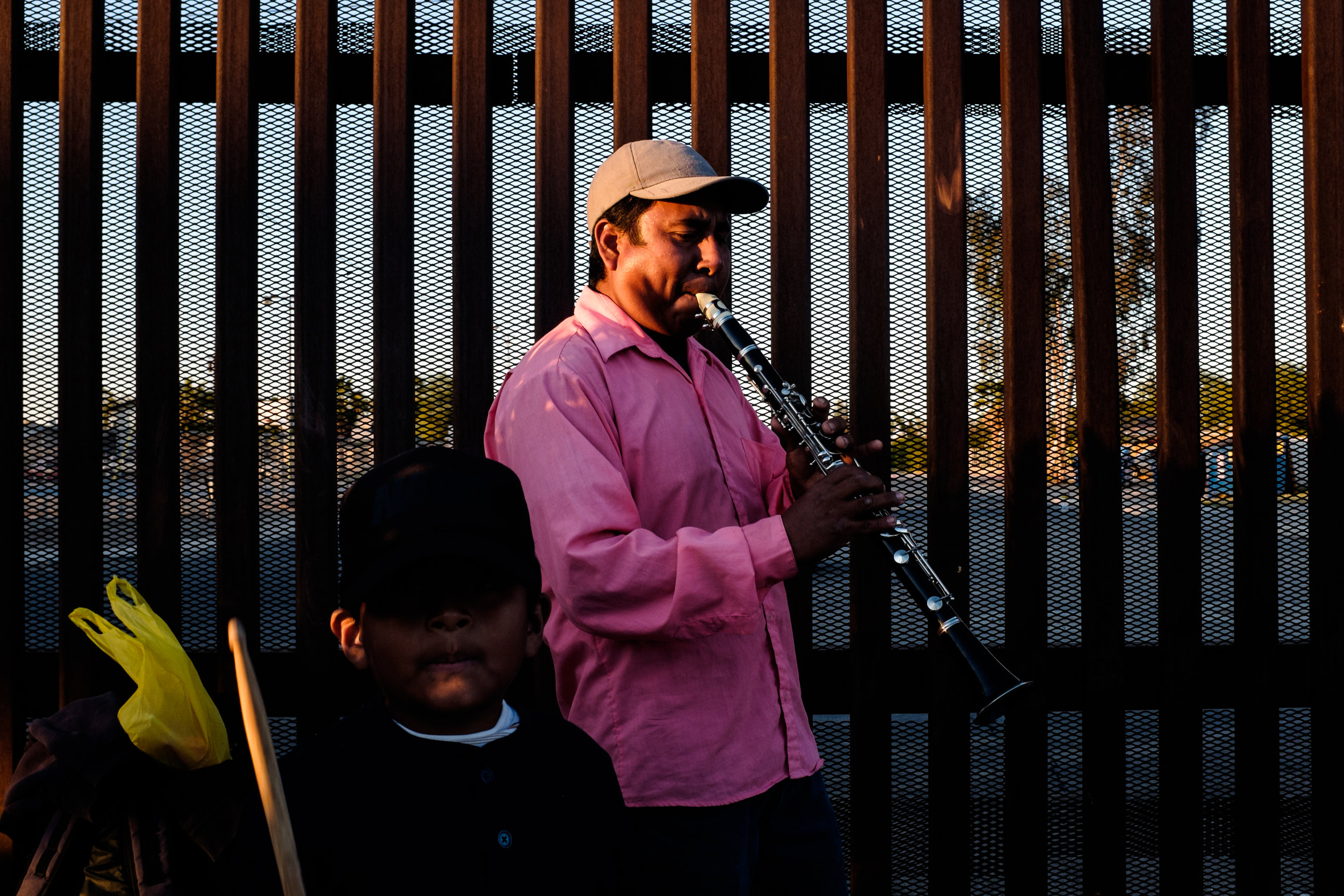 A musician performs for cars waiting on line to cross into the US from Mexicali, Mexico