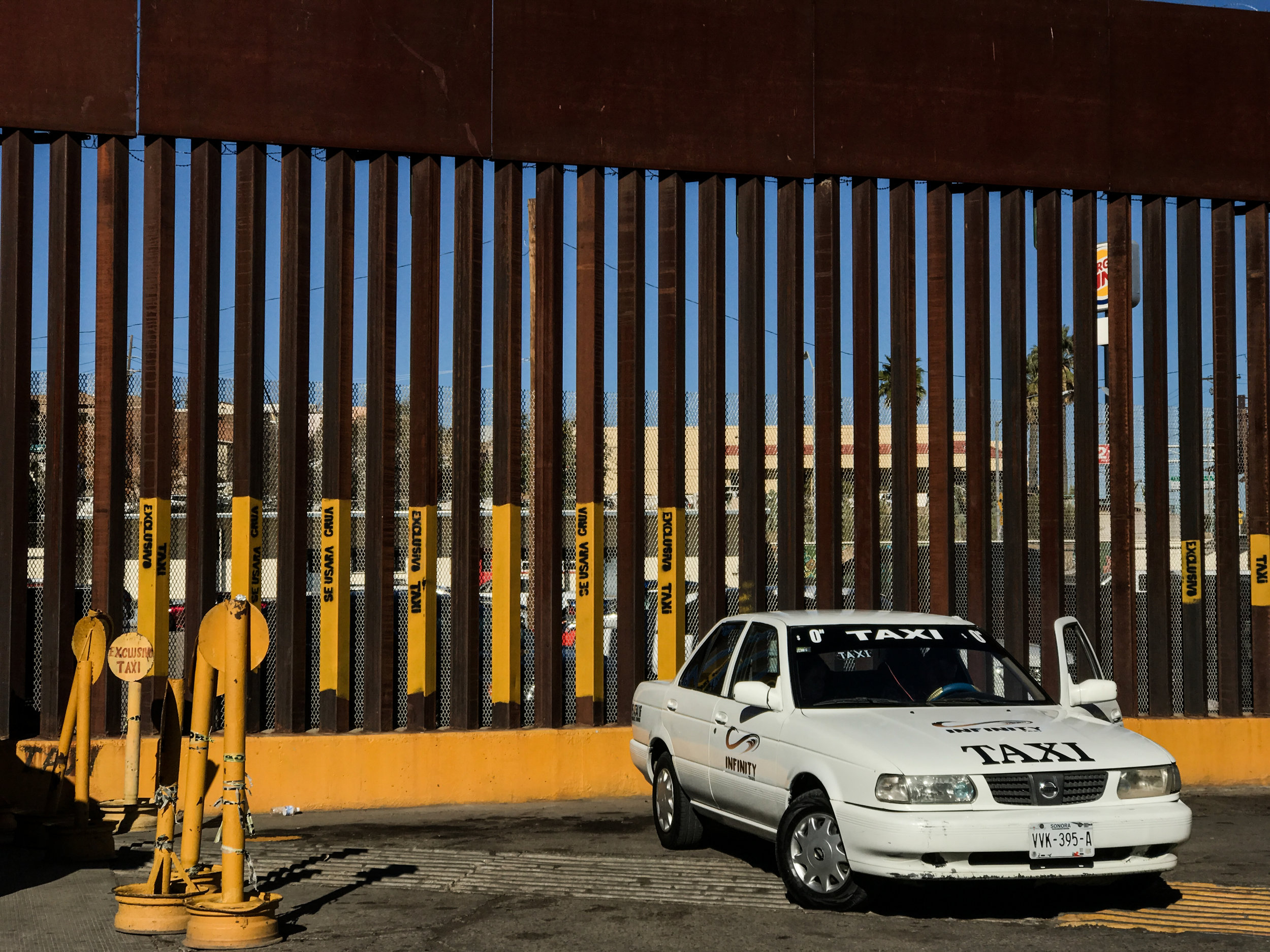 "Signage painted directly on the border fence for a ""taxis only"" parking area in Nogales, Mexico"