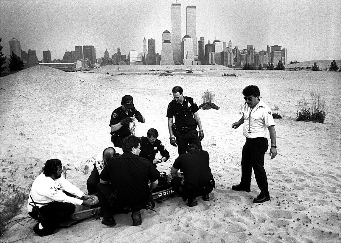 """Jersey City Medical Center Paramedics work to resuscitate a youth who went swimming in the Hudson River and was brought to the surface by rescue divers. The """"beach"""" on the Jersey City waterfront is all luxury housing now. Photograph by Bill Bayer."""