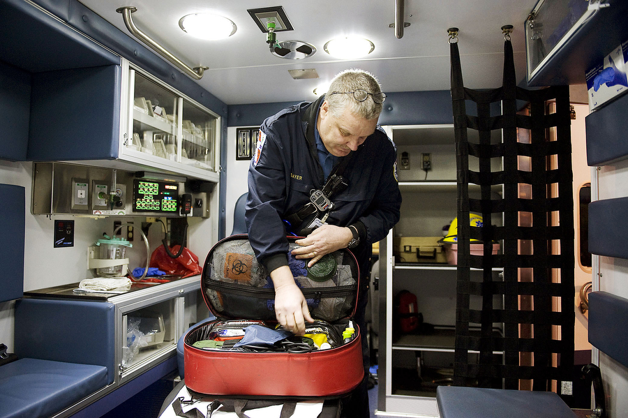 """From the February 7, 2012, Jersey Journal: """"Bill Bayer checks his jump bag, a basic medical kit EMTs carry on every call, at the start of his shift. He began working as an EMT in 2002."""" Photograph by Reena Rose Sibayan /  The Jersey Journal ."""