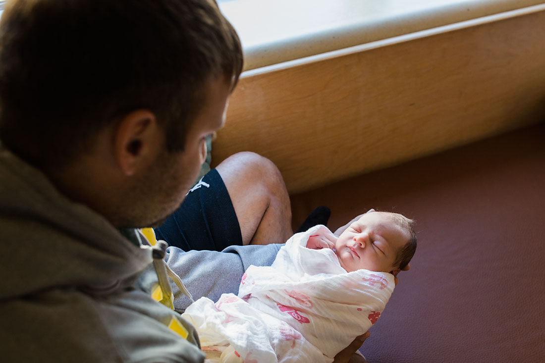 father holding his new baby girl who is one day old