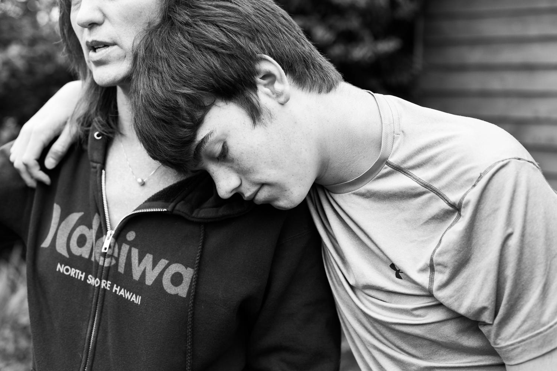 teenage boy leaning against mom