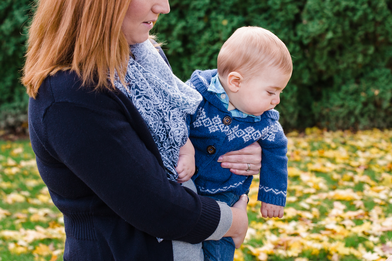 Mother holding her son in a blue sweater