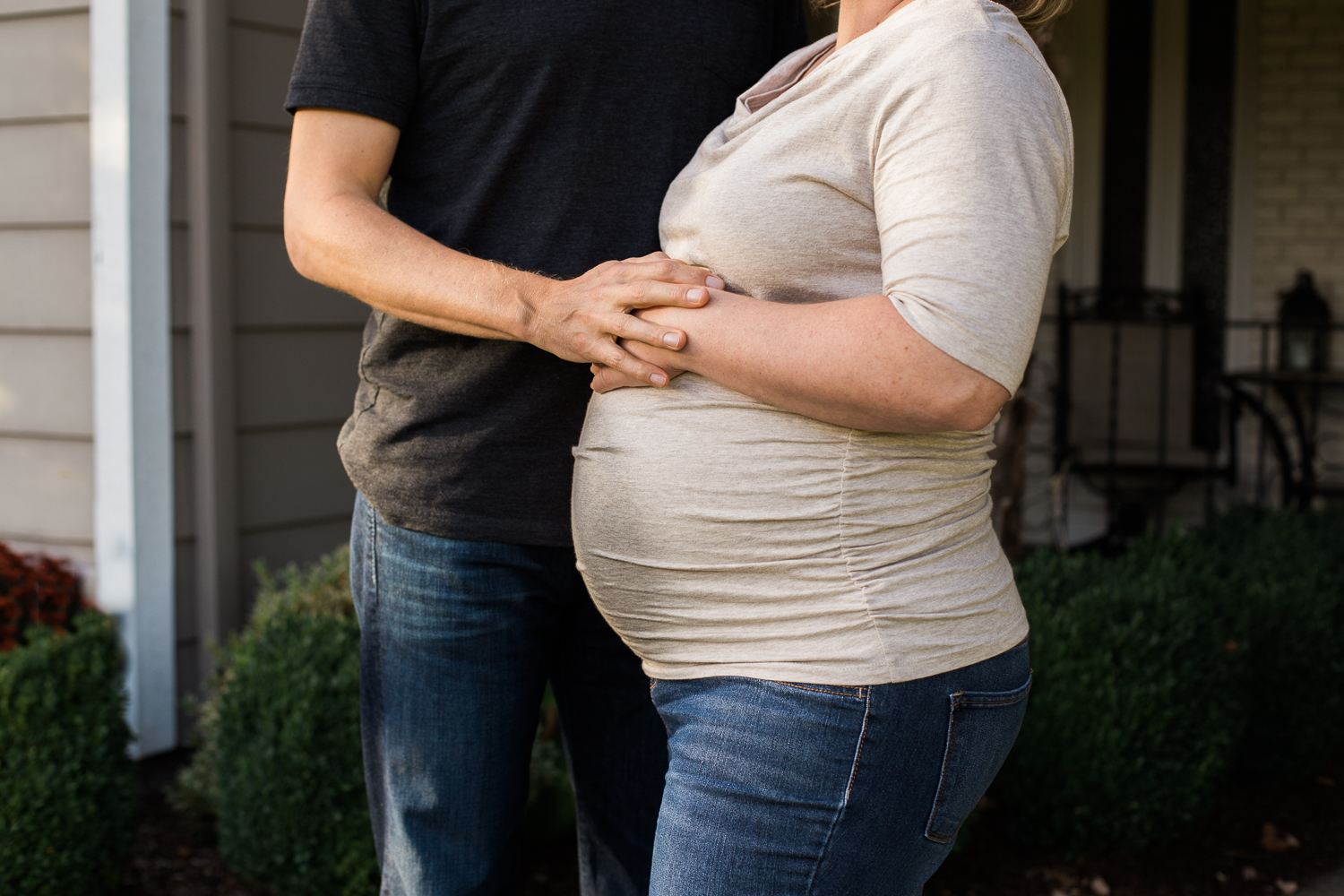 pregnant woman and husband in front yard