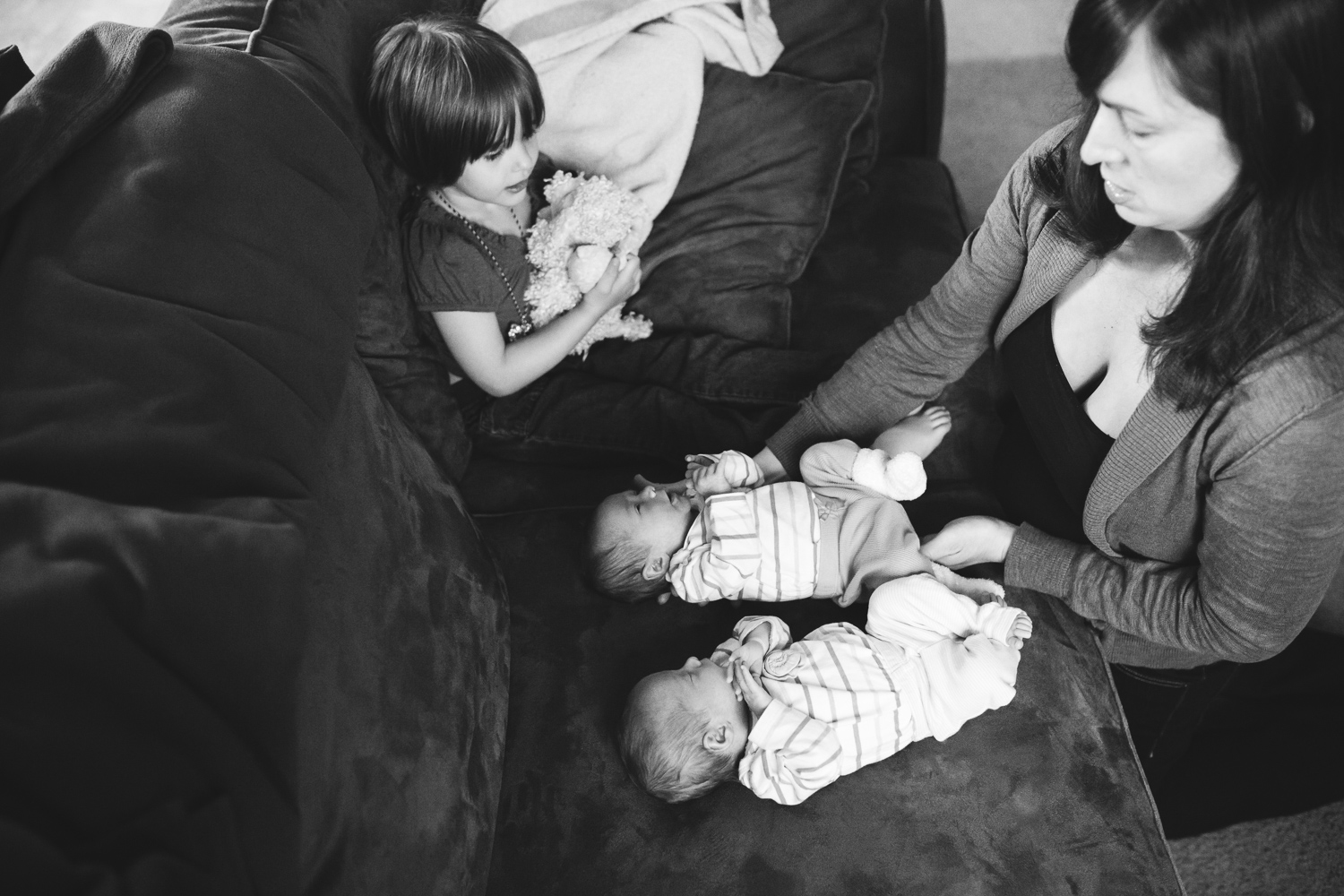 brother and sister holding their twin sisters