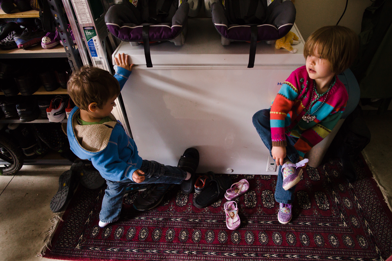 boy and girl putting on their shoes to go outside