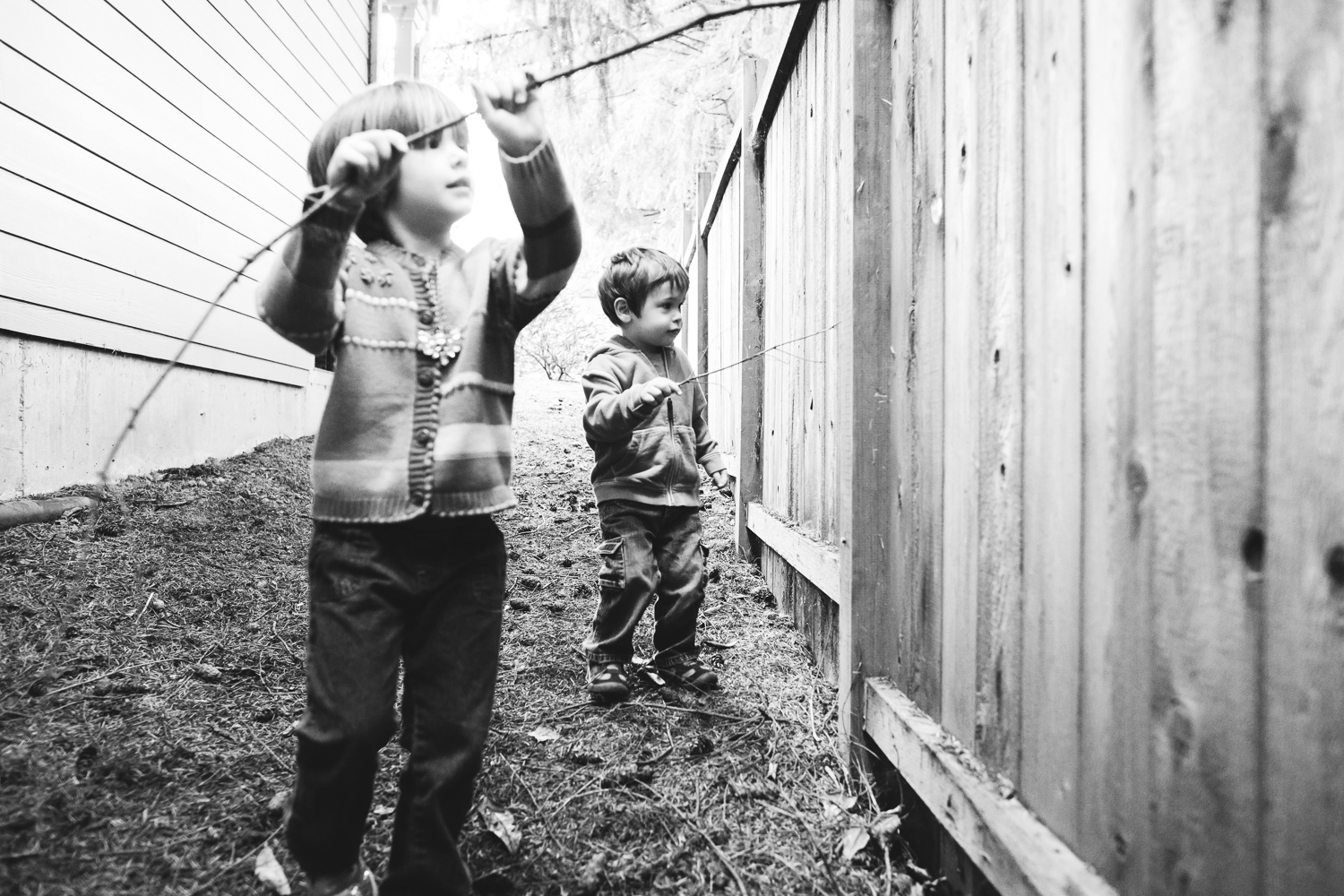 boy and girl playing with sticks outside