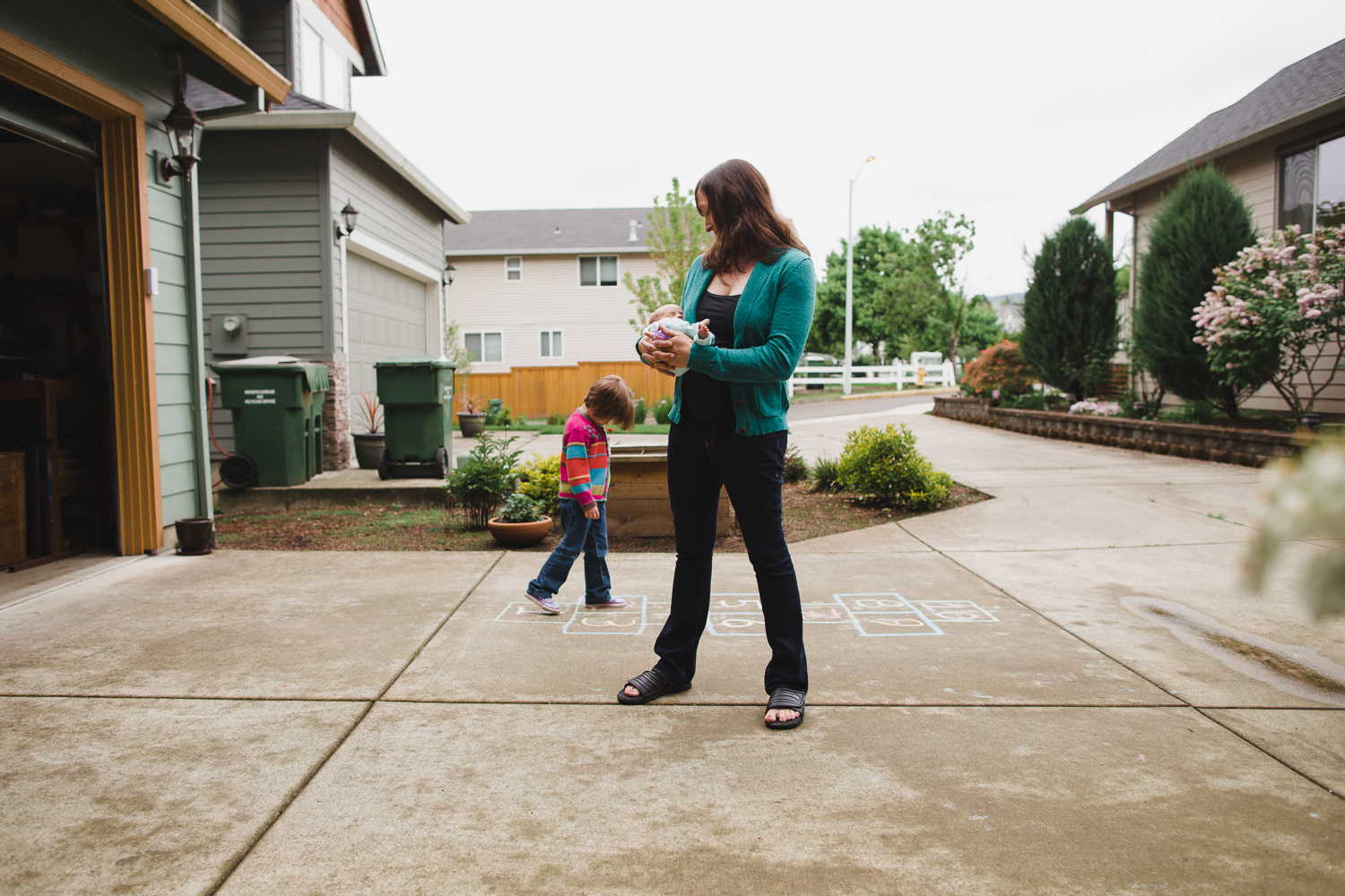 girl playing hopscotch in driveway
