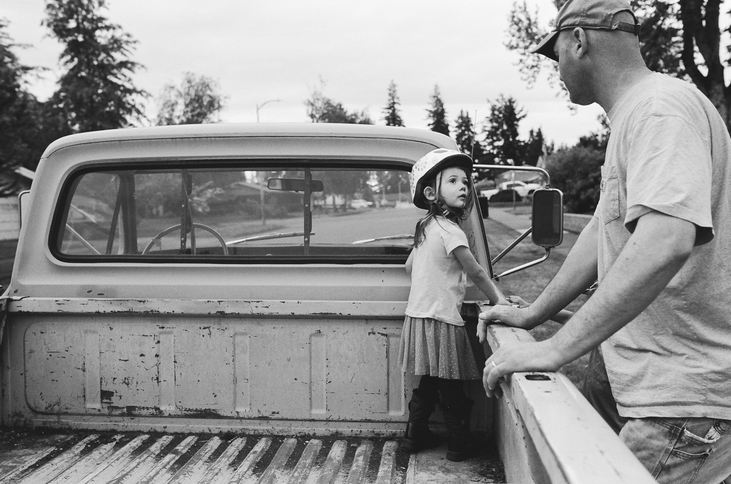 girl playing in the back of her dads truck