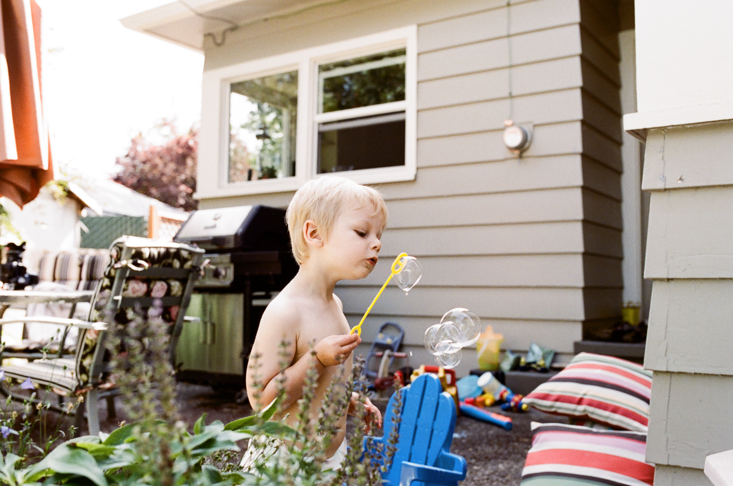 boy playing with bubbles in backyard