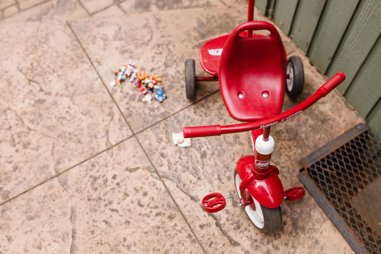 boy pushing his red bike