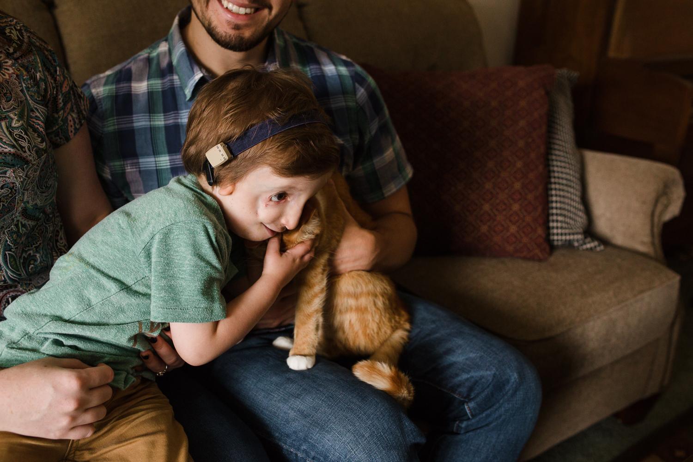 boy hugging orange cat
