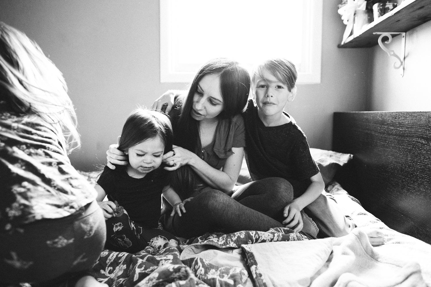 family cuddling on bed