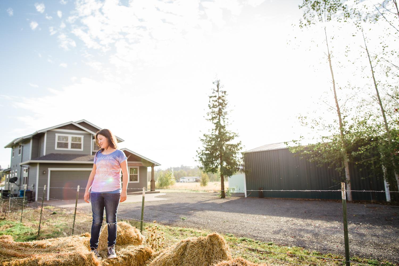 girl standing on top of hay