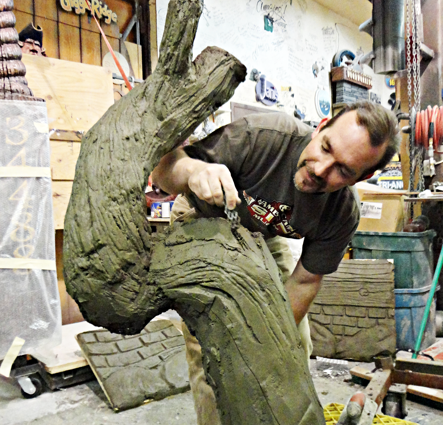 Kurt Stoner from Stoner Graphics carves a concrete tree.