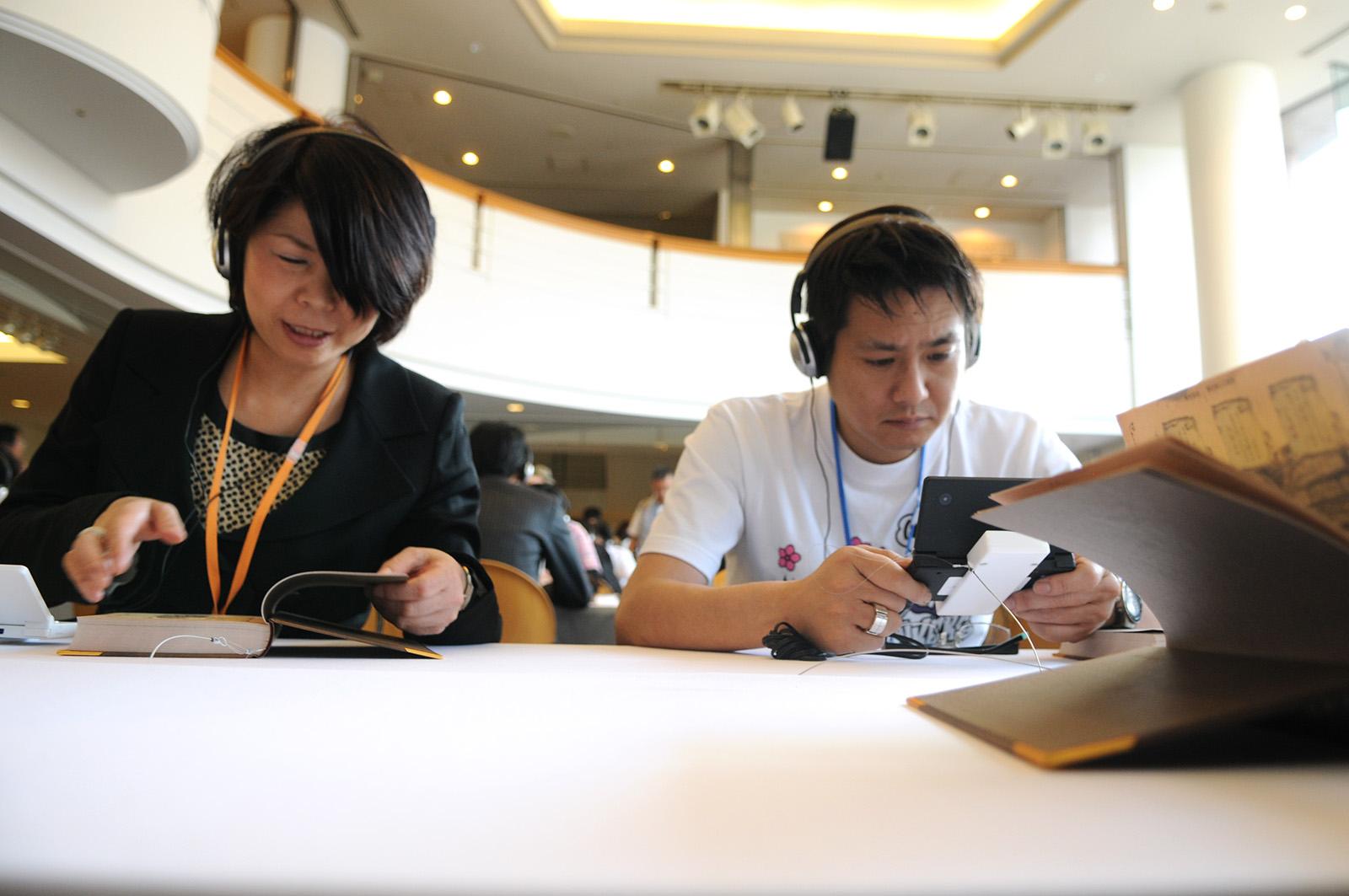 Hisako Akitani, left, and Daisuke Uchiyama play the yet-to-be-released video game Ninokuni on the handheld video console Nintendo DS