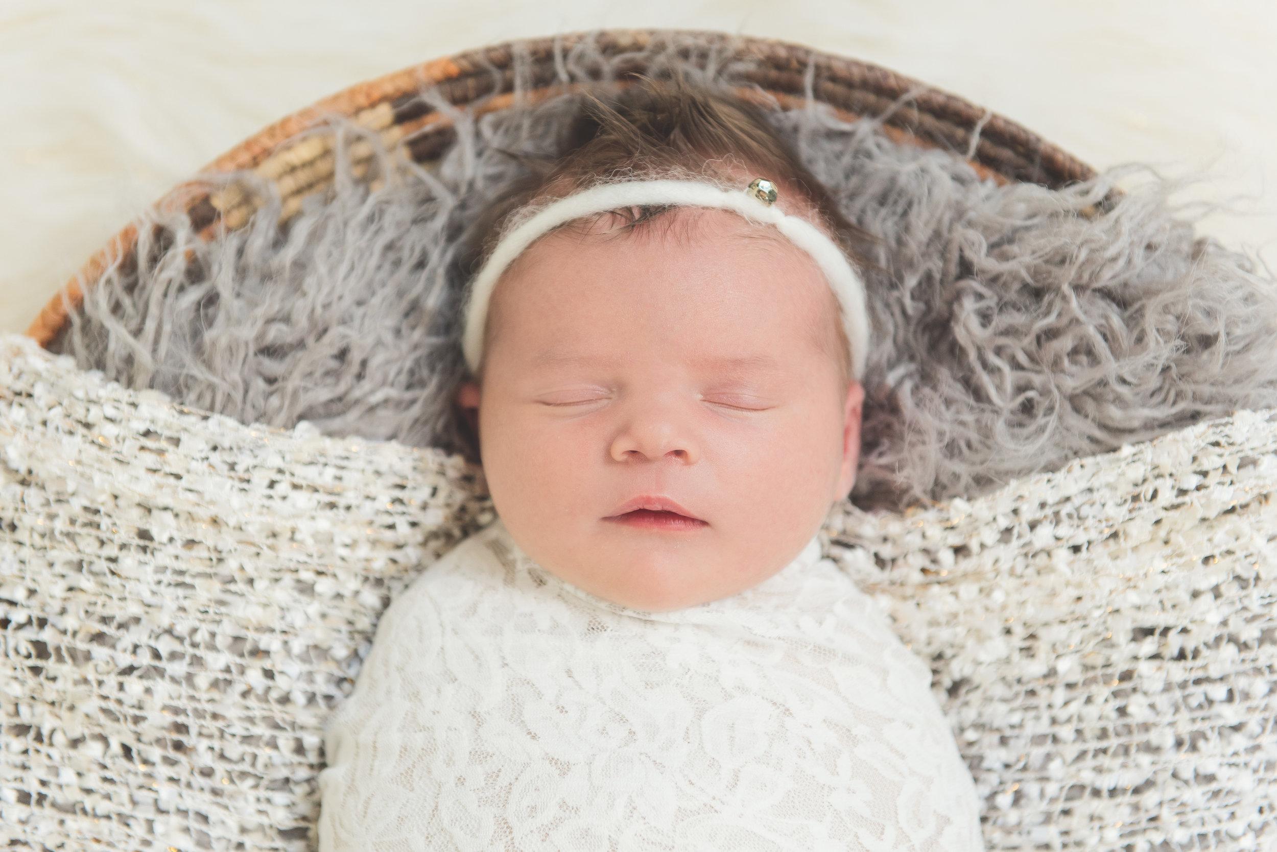 newborn girl in basket with diamond headband