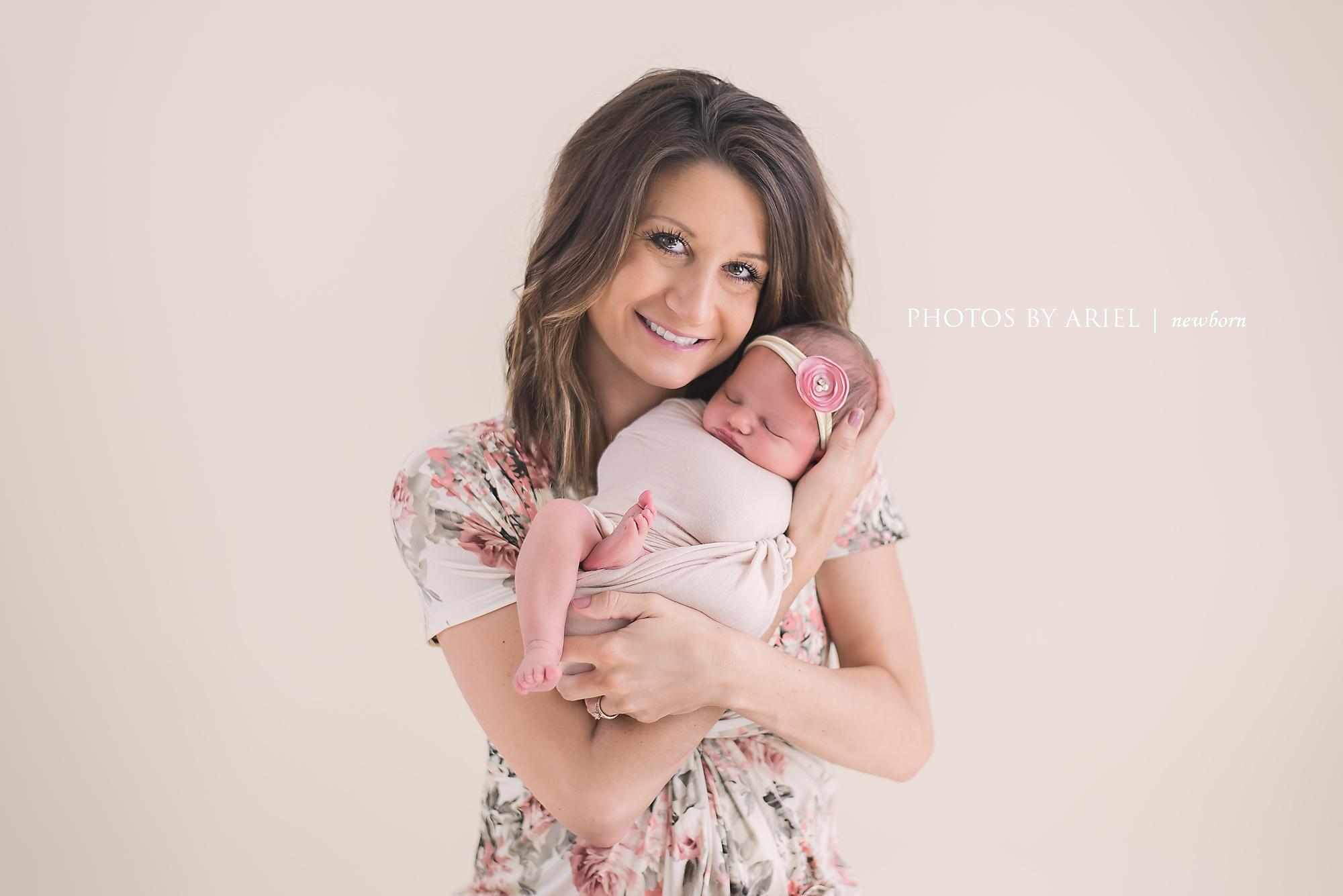 mom snuggling newborn girl
