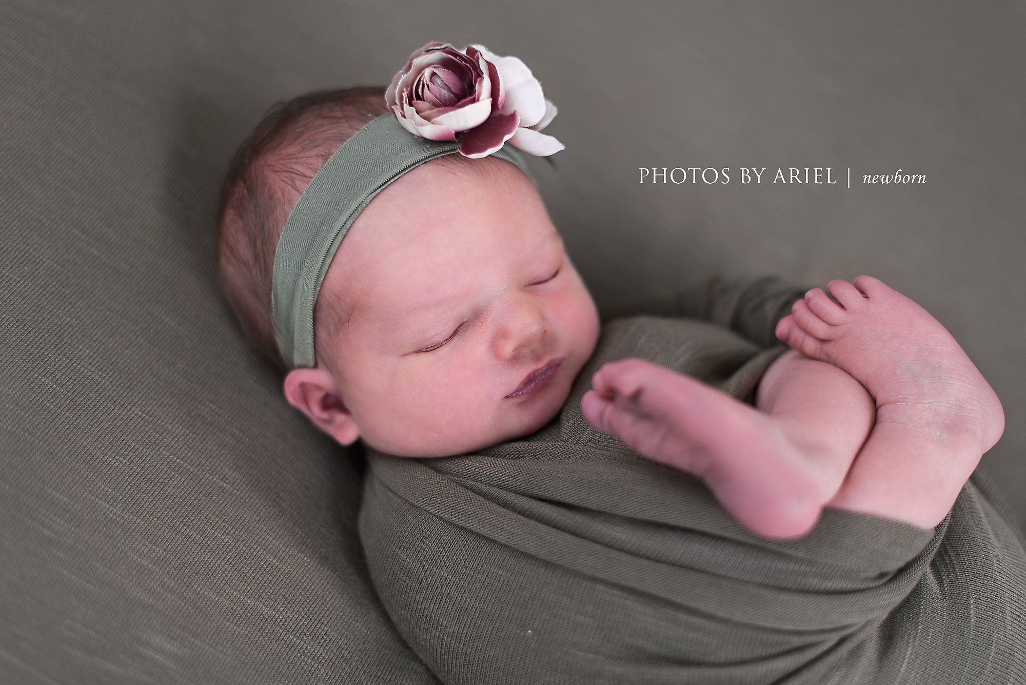 newborn girl with feet hanging out
