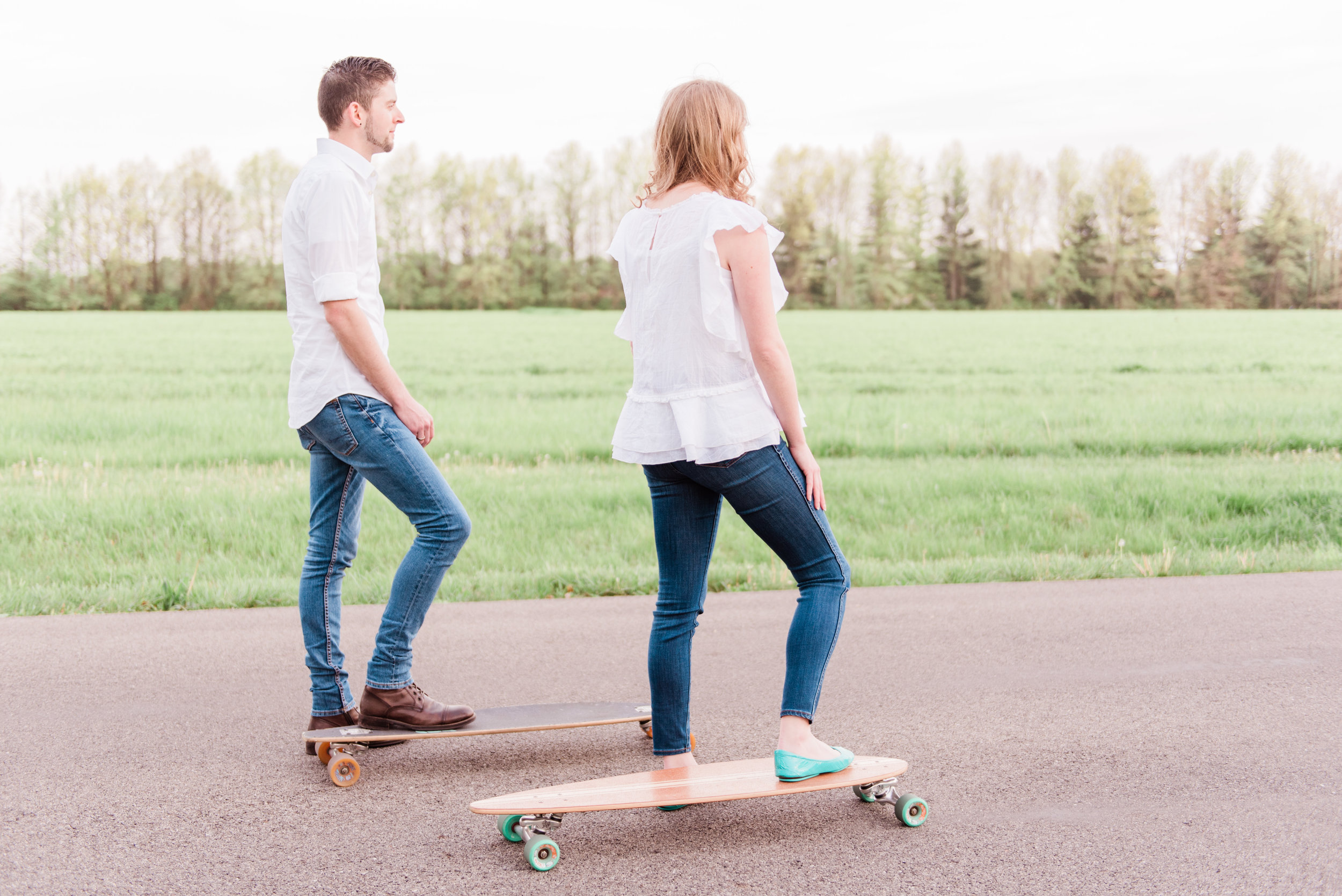 boy and girl longboarding outside