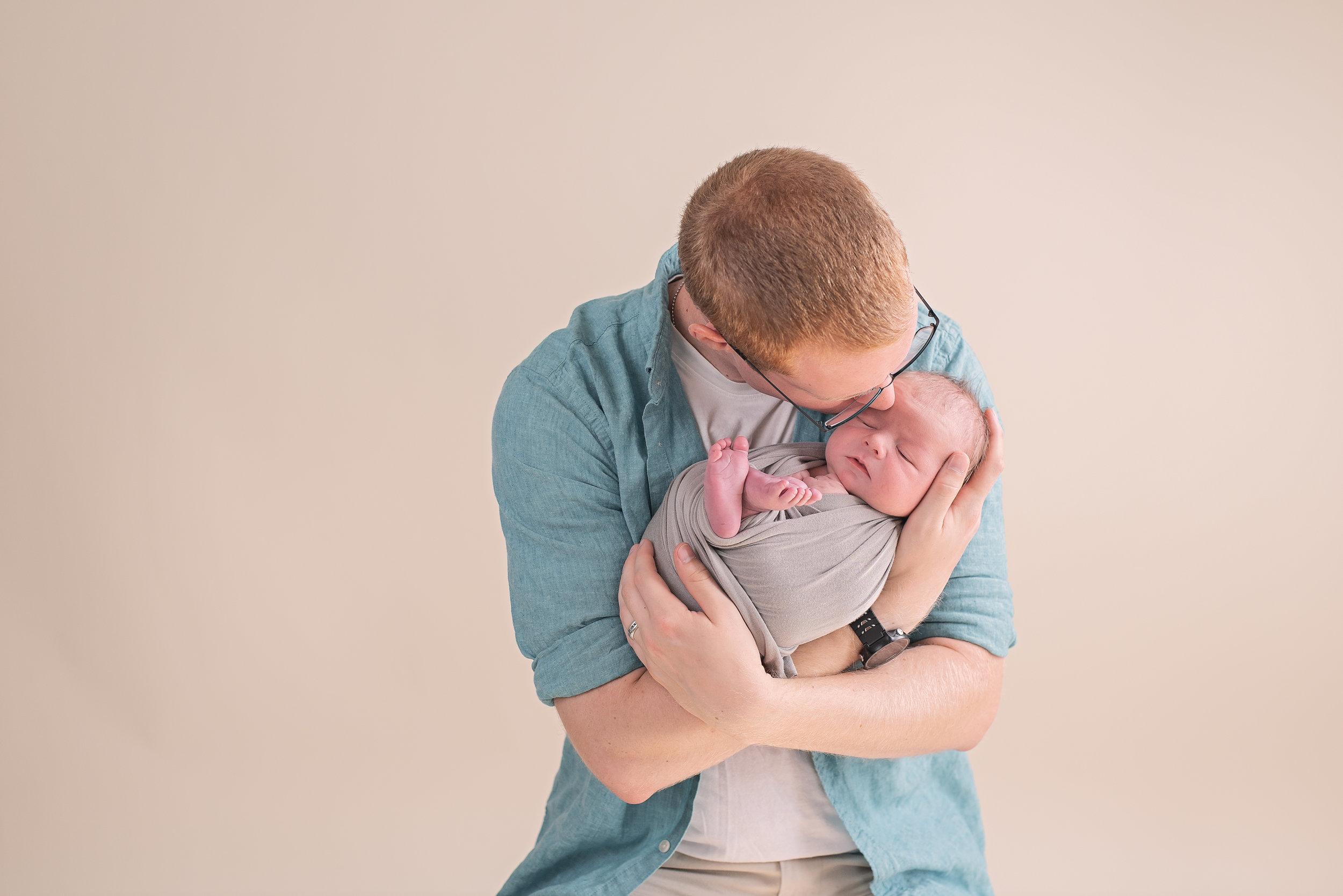 dad kissing newborns head